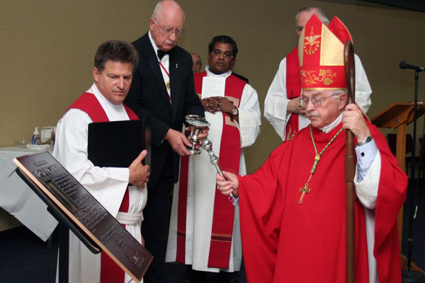 Mike McDougall (second from left) of Father Albert Newman Council 8470 in Calgary, Alberta, holds an aspersorium of holy water while Bishop Frederick B. Henry of Calgary blesses a plaque commemorating the Knights' contribution to the new Father Michael J. McGivney Hall at St. Mary's University College. Also pictured are: Father Kevin Tumback (far left) and Father Leo Felix Monroe (center).